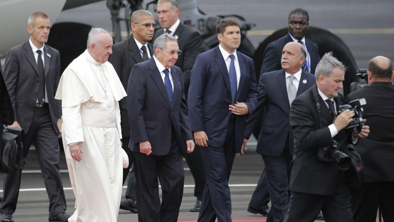 Surrounded by security and government press, Pope Francis walks with Cubas President Raul Castro as he arrives to the airport in Havana, Cuba, Saturday, Sept. 19, 2015.AP Photo/Ramon Espinosa