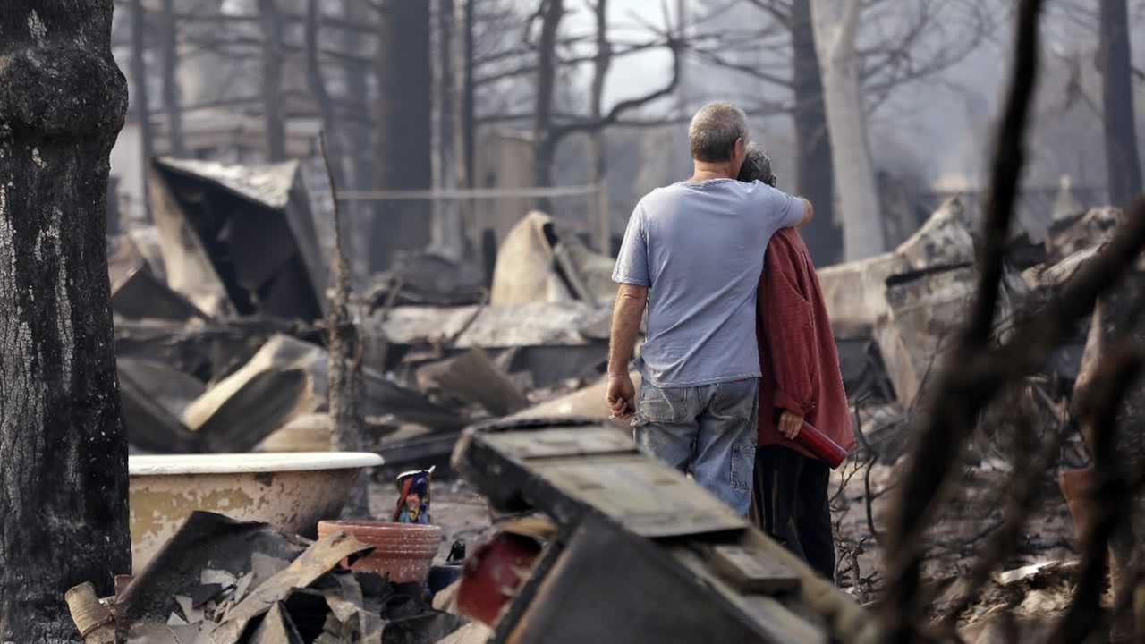 Richard and Kathie Reeves embrace as they stand in the remains of the home of close friends that was destroyed several days earlier, Tuesday, Sept. 15, 2015, in Middletown, Calif.