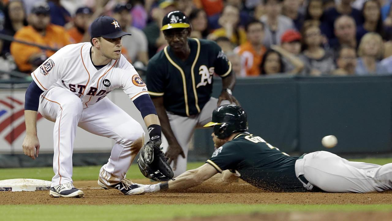 Athletics Craig Gentry slides under the ball for an RBI-triple as Astros Jed Lowrie reaches for the ball during a game on Sept. 19, 2015, in Houston. (AP Photo/Pat Sullivan)