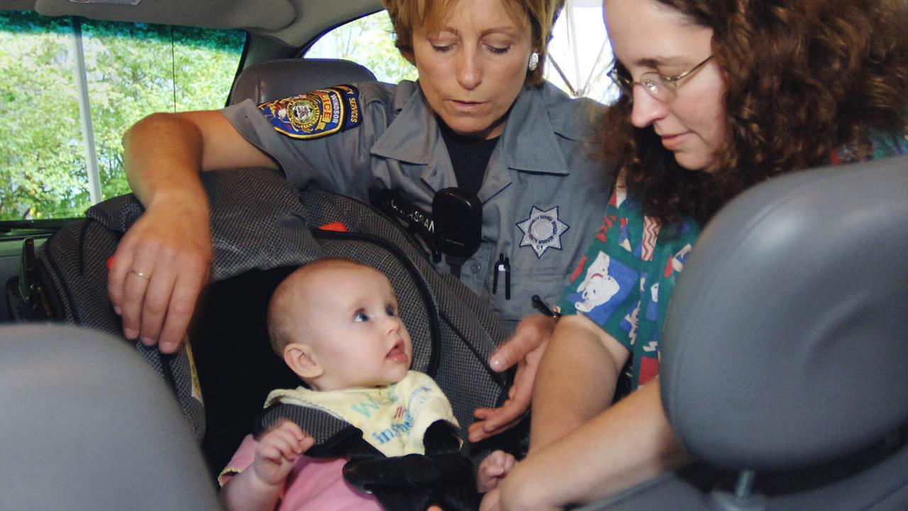 FILE - Officer Robin Massanti helps Debra Mlinek from Suffield secure her daughter, Eliza, five months, in her car seat during a Child Passenger Safety Clinic.