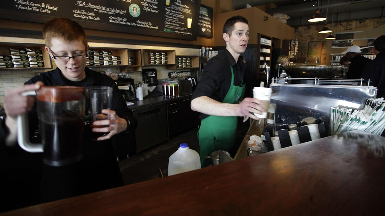 Baristas Lindsey Pringle, left, and Josh Barrow, right, prepare iced and hot Starbucks drinks, at a Starbucks Corp. store in Seattle, Friday, April 27, 2012.  (AP Photo)