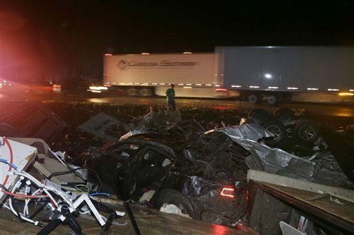 """<div class=""""meta image-caption""""><div class=""""origin-logo origin-image """"><span></span></div><span class=""""caption-text"""">A man walks past a wrecked automobile and RV on Interstate 40 in Mayflower, Ark., Sunday, April 27, 2014. A powerful storm system rumbled through the central and southern United States on Sunday, spawning a massive tornado (AP Photo/Danny Johnston)</span></div>"""