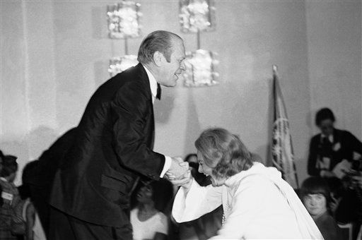 President Gerald Ford gives television personality Barbara Walters a helping hand as she slips while stepping onto the stage during an awards presentation March 10, 1975. <span class=meta>AP Photo/ Anonymous</span>