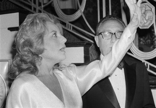Barbara Walters raises her arm as she reacts to something she sees as she stands next to Dr. Henry Kissinger at a dinner honoring the former secretary of state on May 3, 1980. <span class=meta>AP Photo/ PEC</span>