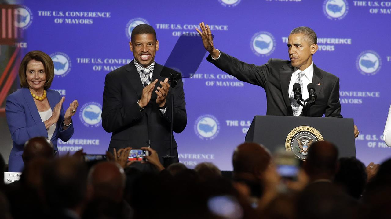 President Obama waves at the U.S. Conference of Mayors as House Minority Leader Nancy Pelosi and Sacramento, Calif., Mayor Kevin Johnson, center, watch Friday, June 19, 2015