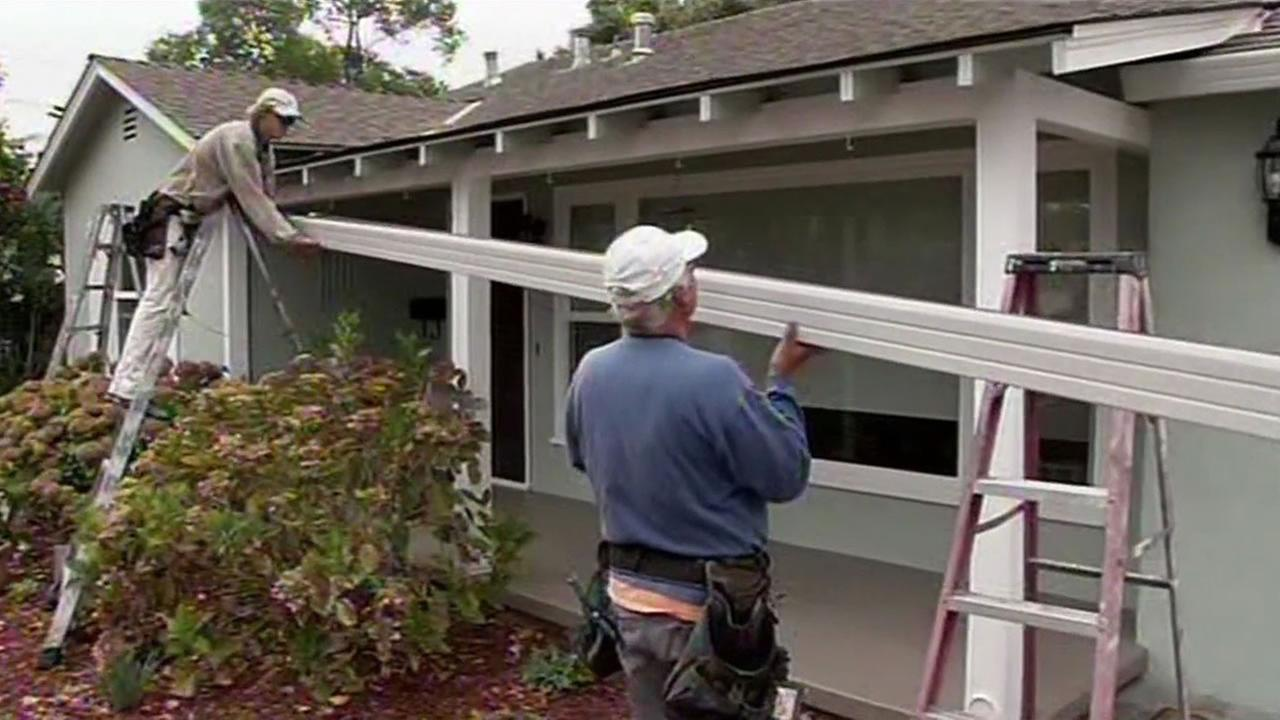 FILE - Two men replace gutters on a home in the Bay Area in this undated image.