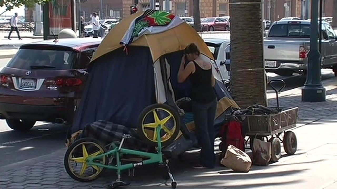 FILE - A homeless person stands next to a tent on a San Francisco,Calif. street in this undated image.