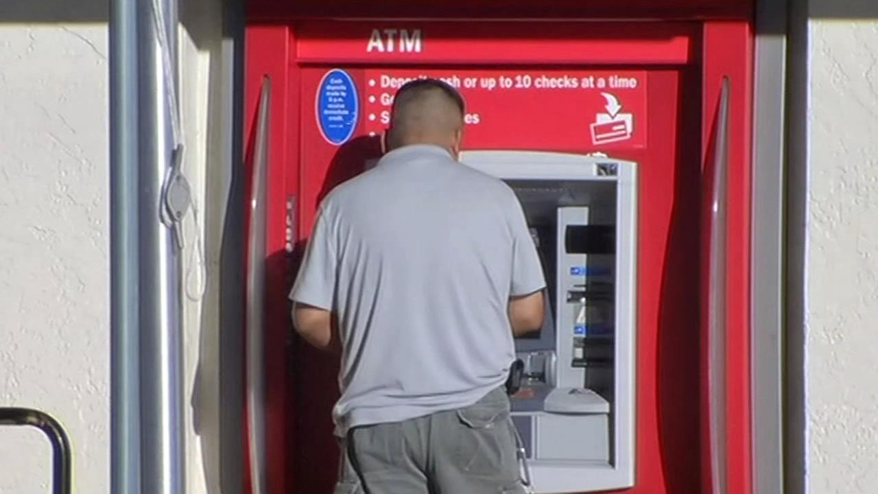 FILE - A man stands at an ATM machine in San Leandro in this undated image.