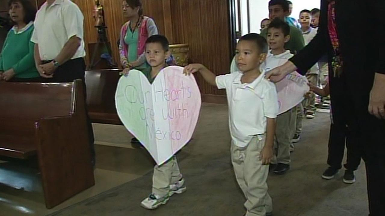 Two boys walk into a church with a sign saying Our hearts are with Mexico