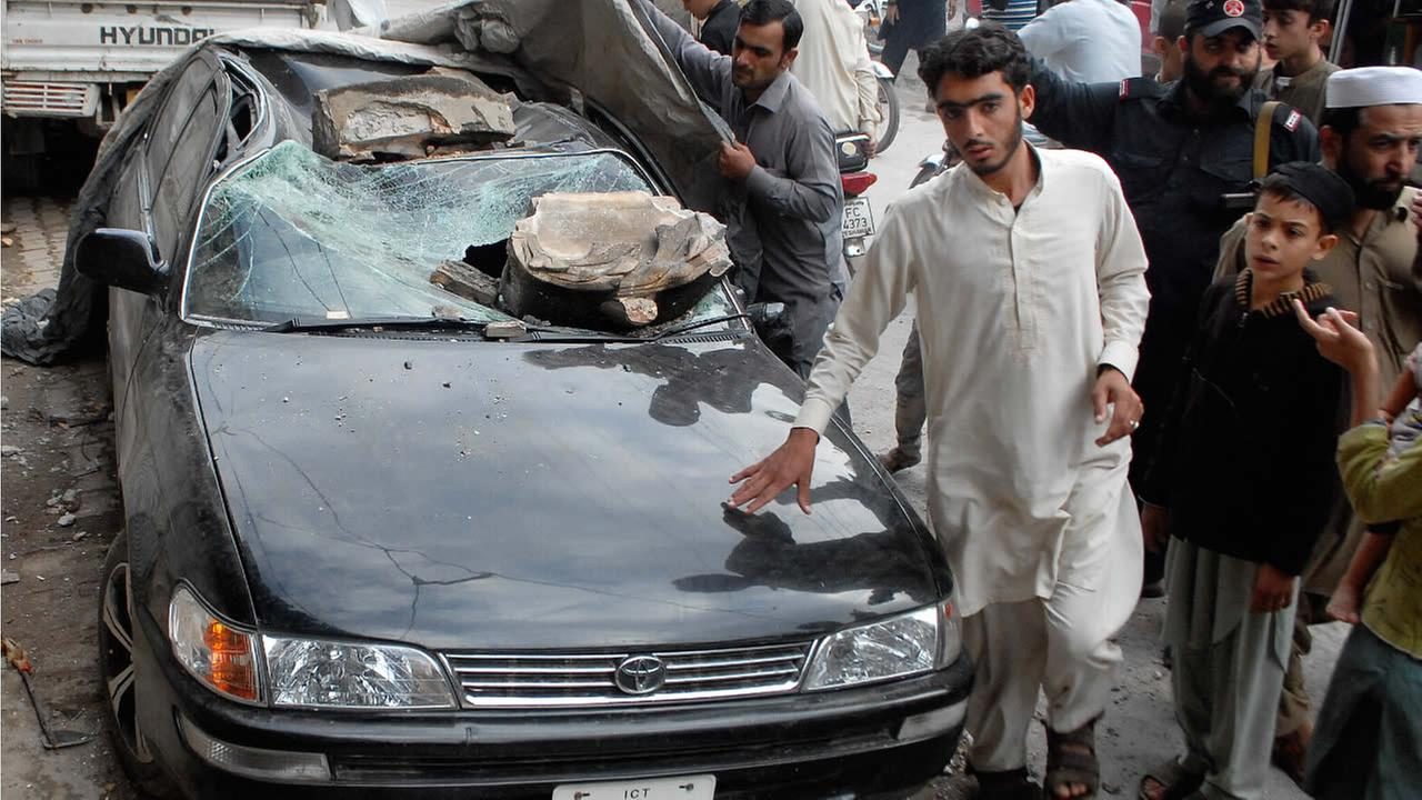 People stand near a car damaged from an earthquake in Peshawar, Pakistan, Monday, Oct. 26, 2015 after a powerful earthquake struck northern Afghanistan. (AP Photo/Mohammad Sajjad)