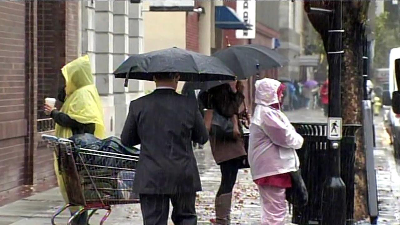 People are seen holding umbrellas during a storm in the Bay Area on Monday, November 2, 2015.