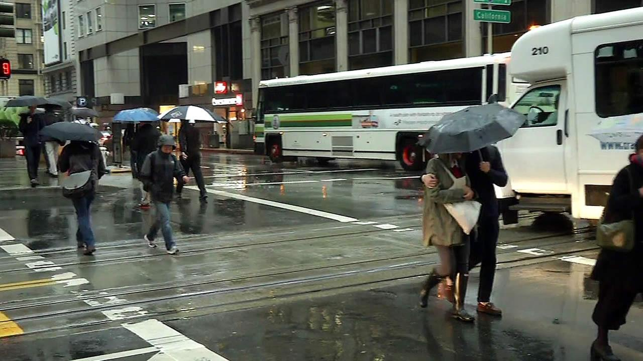 In this image, people holding umbrellas cross the street during a storm in San Francisco, Calif. on Monday, November 9, 2015.