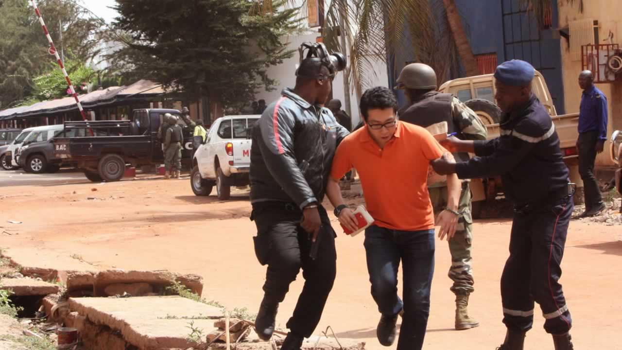 Mali trooper assist a hostage, centre, to leave the scene, from the Radisson Blu hotel to safety after gunmen attacked the hotel in Bamako, Mali, Friday, Nov. 20, 2015.