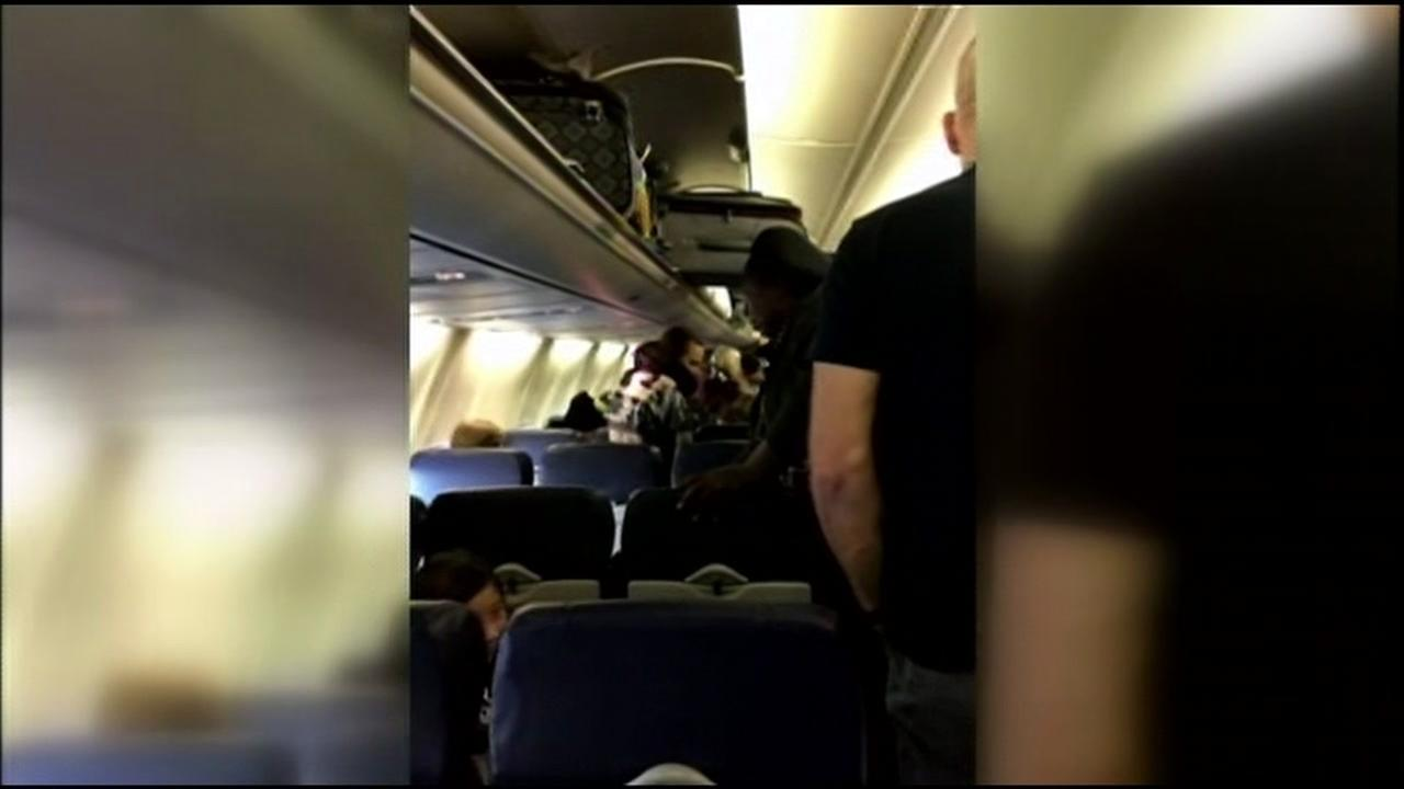 Cellphone video shows the inside of a Southwest plane that got diverted after a report of three passengers acting suspiciously on Sunday, November 22, 2015.