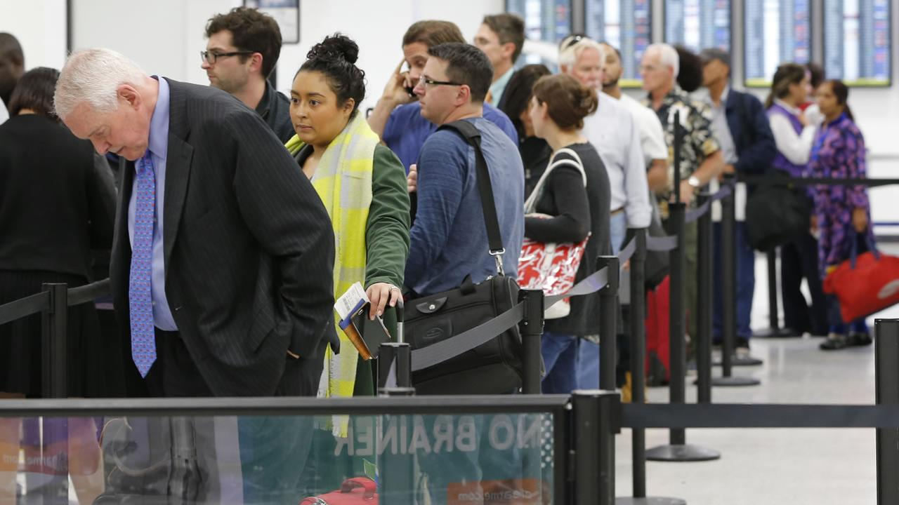 FILE: Travelers line up at a TSA checkpoint on Tuesday, Nov. 24, 2015, in Miami. Thanksgiving is one of the busiest travel holidays of the year.