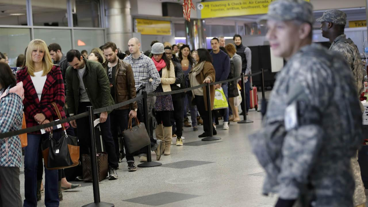 Security personnel looks on as passengers wait to pass through airline security at LaGuardia Airport in New York, Wednesday, Nov. 25, 2015.