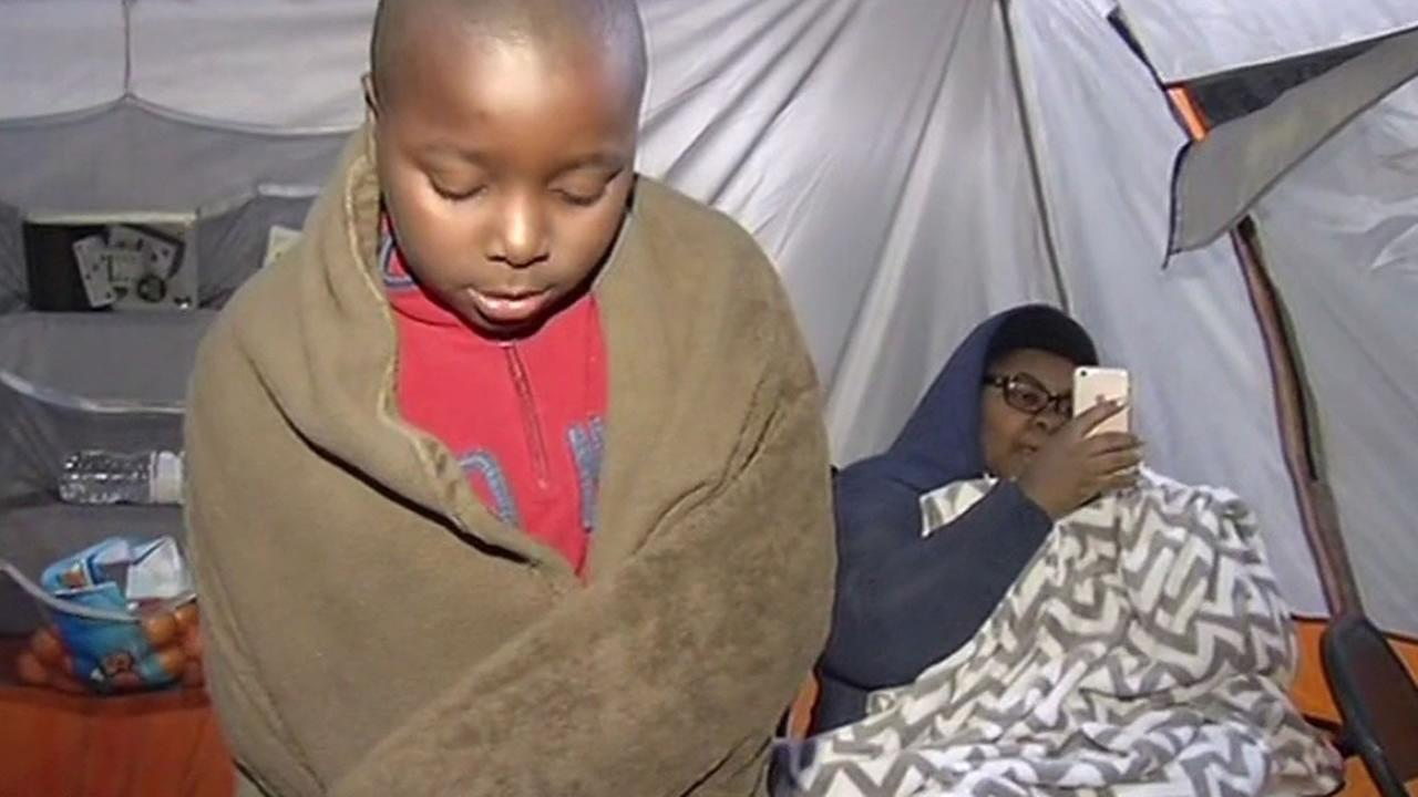 a child wraps himself up in a blanket