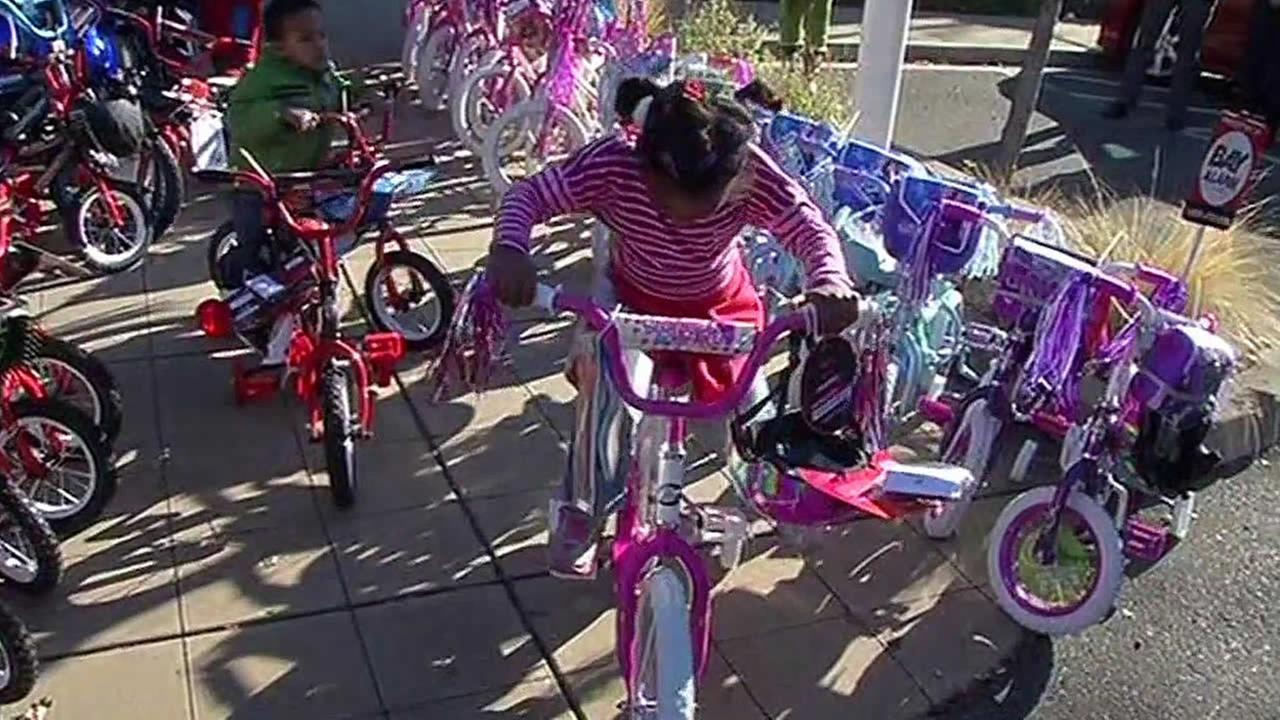 Two kids are seen with donated bikes outside Bay Alarm in Pacheco, Calif. on Wednesday, December 16, 2015.