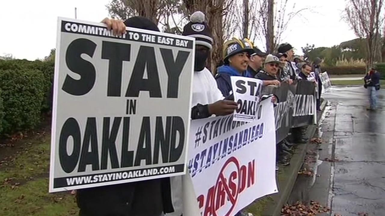 Oakland Raiders hold signs saying stay in Oakland