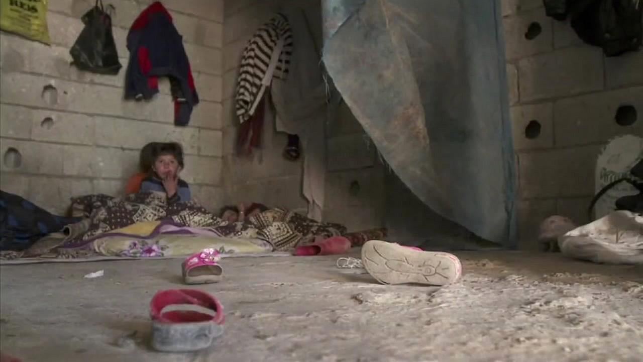 Syrian refugees are seen sitting on a floor in this undated image.