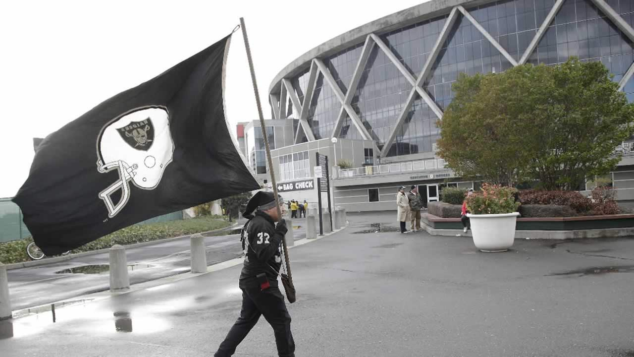 An Oakland Raiders fan holds a flag outside the O.co Coliseum in Oakland, Calif. in this undated image. (AP Photo)
