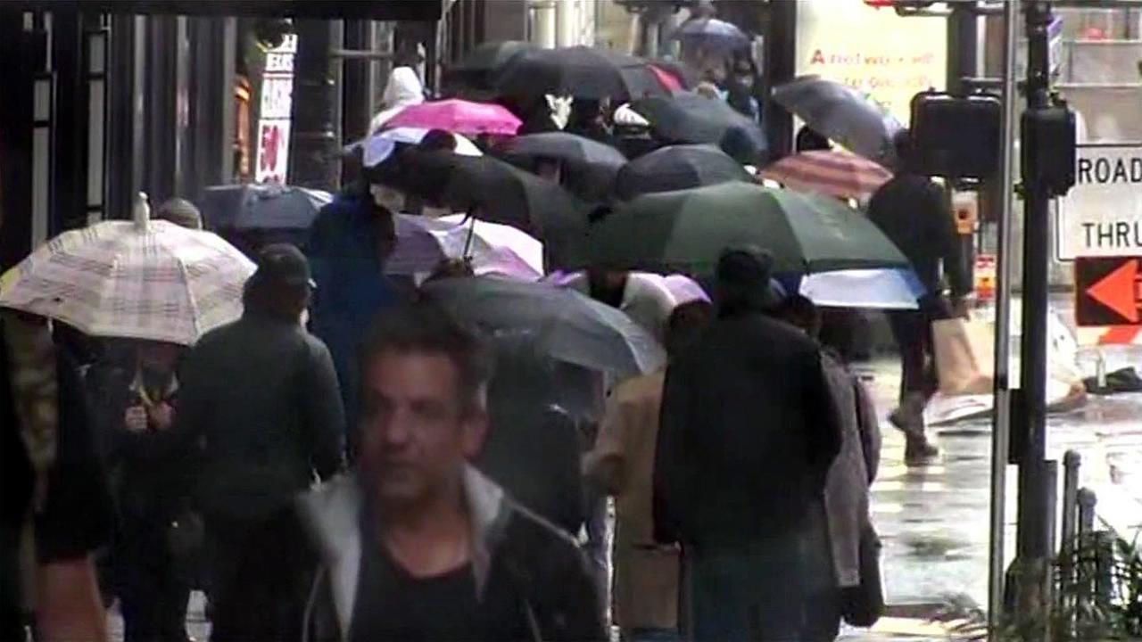 A crowd walks on a busy street in San Francisco, Calif. during a storm on Sunday, January 17, 2016.