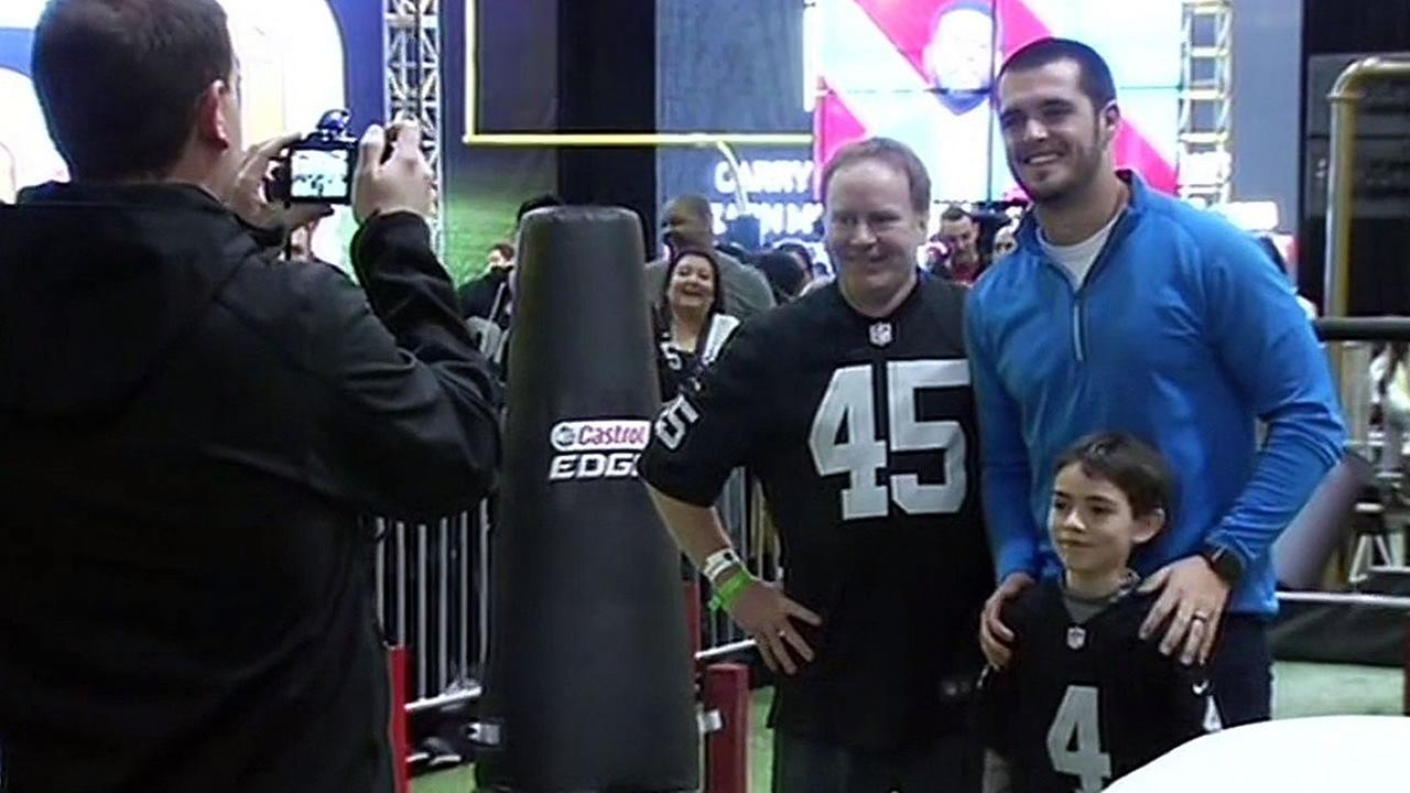 Oakland Raiders quarterback Derek Carr takes a photo with fans