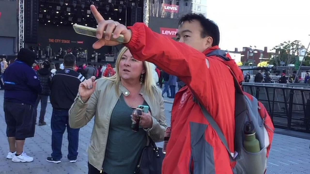 Super Bowl 50 volunteer points out directions for a woman