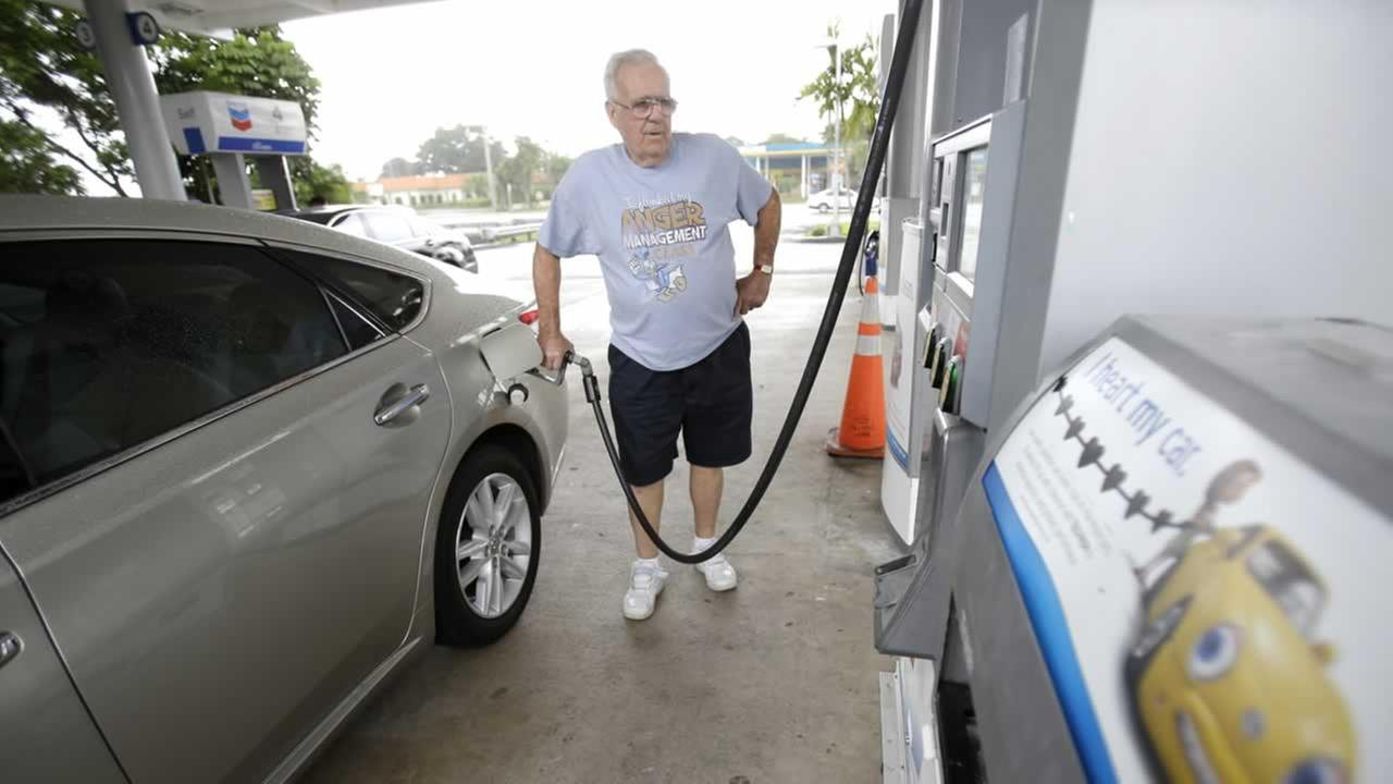 In this Wednesday, June 4, 2014 photo, Marty Mascio, of Pembroke Pines, Fla., pumps gasoline into his car at a Chevron gasoline station in Pembroke Pines, Fla.