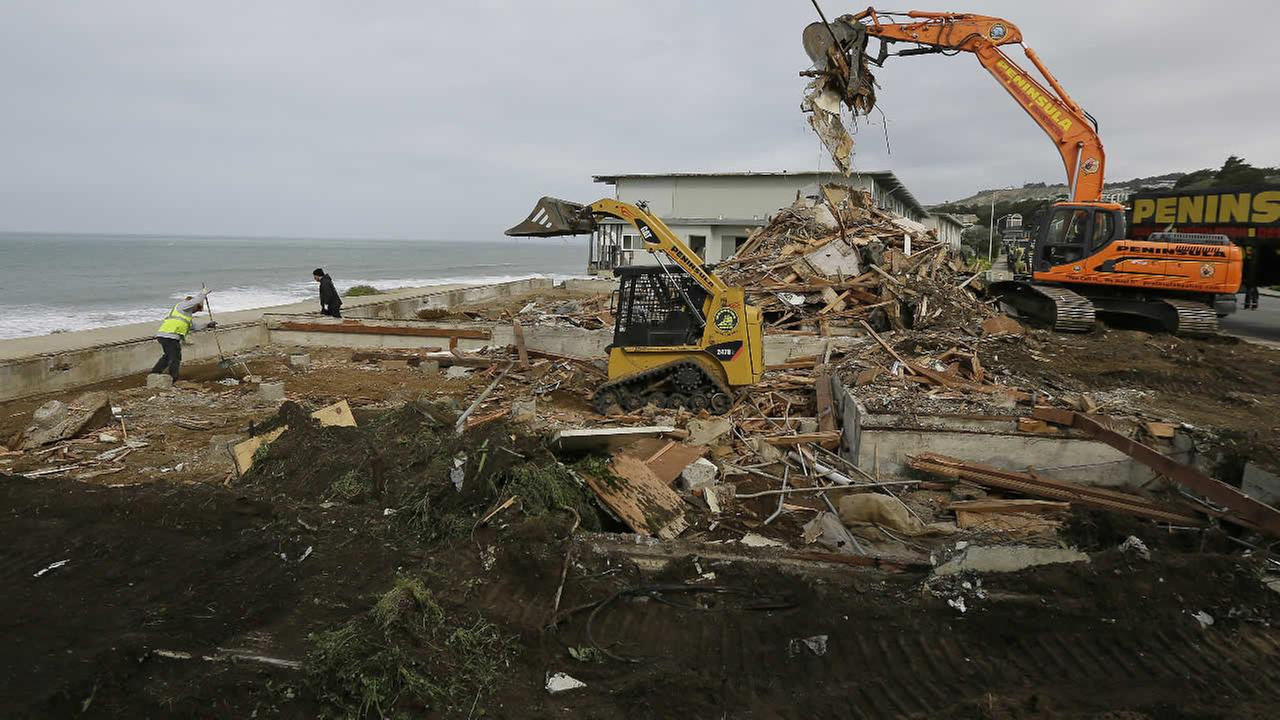 A crew clears away debris from a demolished cliffside apartment that massive erosion had left teetering on the edge of a cliff overlooking the Pacific Ocean, Friday, Feb. 19, 2016, in Pacifica, Calif. AP Photo/Eric Risberg