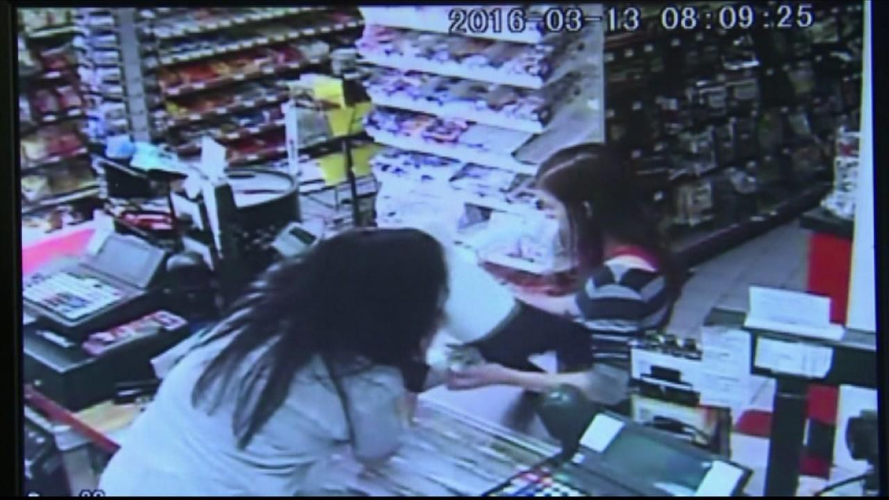 A store clerk rescued a  baby from its mothers arms after she began to have a seizure.