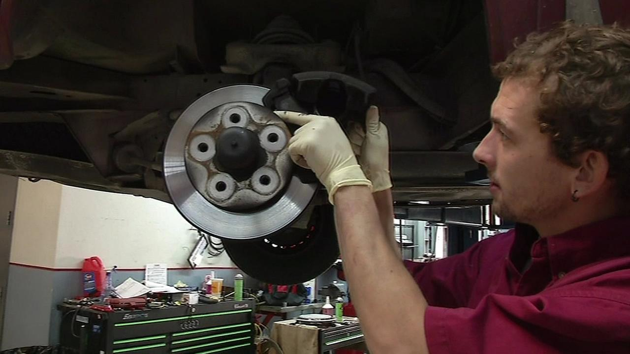 A mechanic is seen putting brake pads on a car at an auto shop in this undated image.