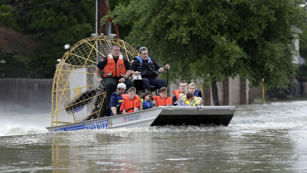 Residents are evacuated from their flooded neighborhoods by airboat, Tuesday, April 19, 2016, in Spring, Texas.