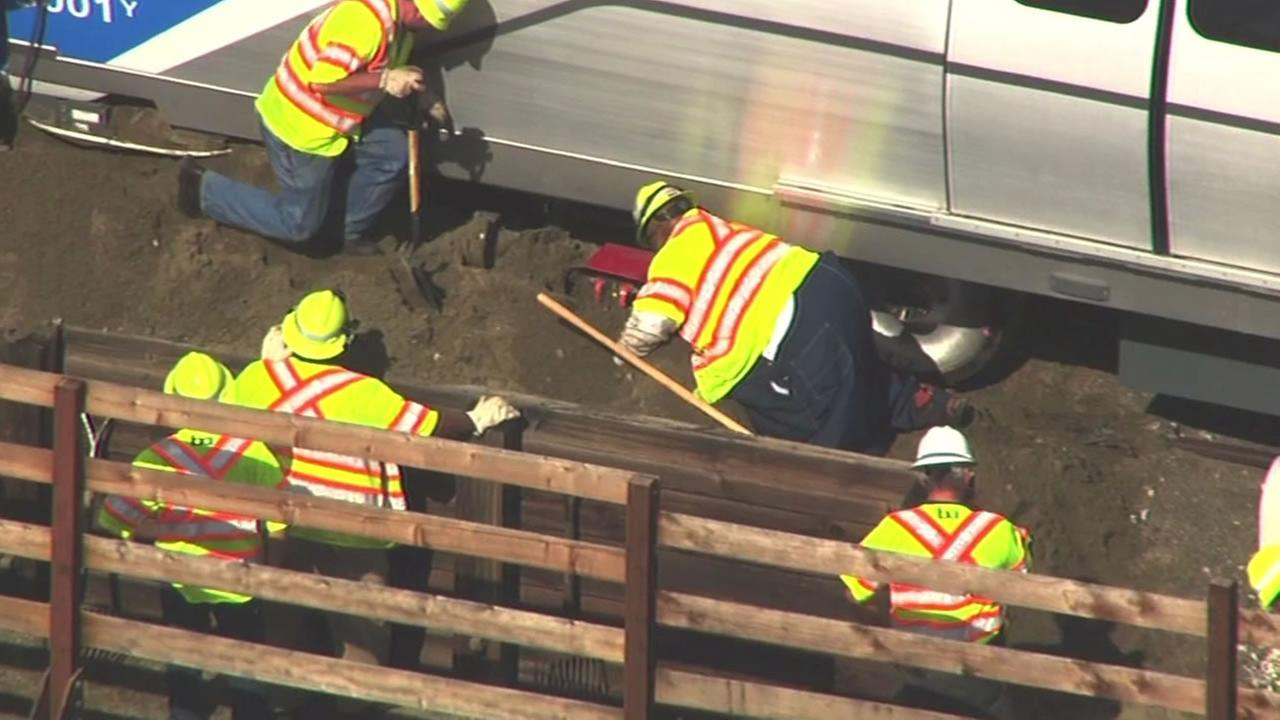 This image shows crews working to remove dig out a new BART train from dirt after it stopped in a mound of dirt at the end of a test track in Hayward, Calif. April 22, 2016.