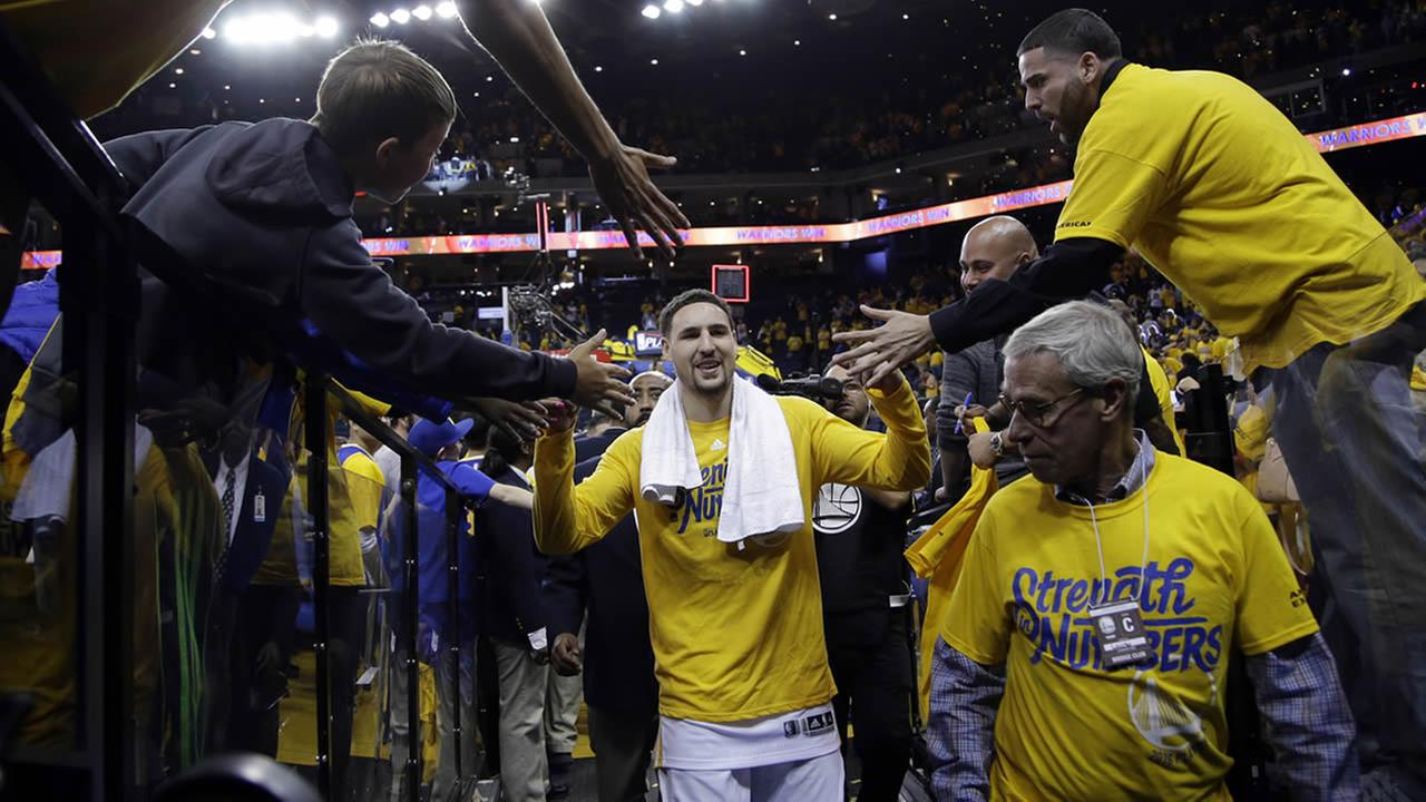 Warriors Klay Thompson celebrates with fans after the teams 114-81 win over the Houston Rockets in Game 5 of their playoff series on April 27, 2016, in Oakland, Calif. (AP Photo)