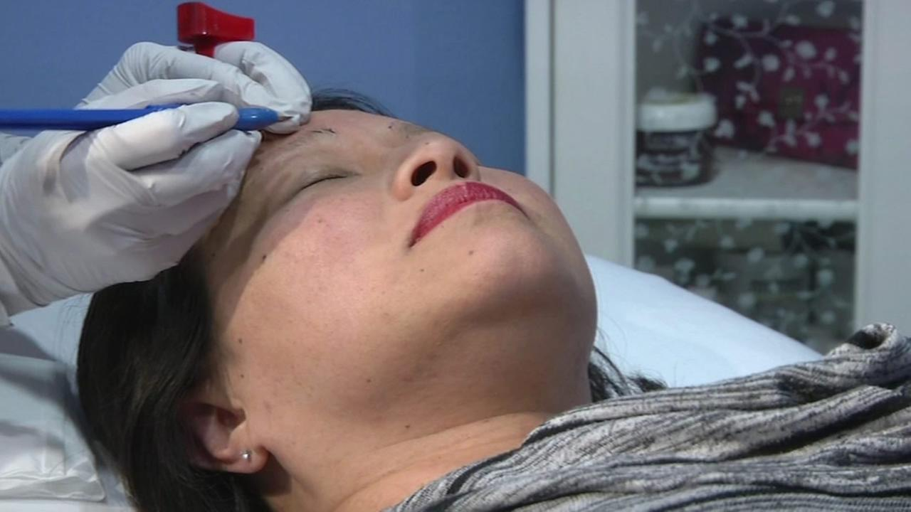 A woman is seen undergoing a procedure known as microblading in this undated image.