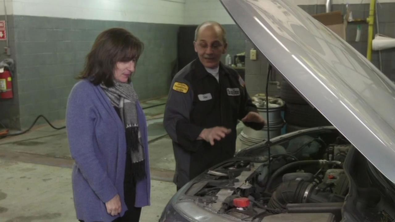 This undated image shows a woman meeting with a mechanic.