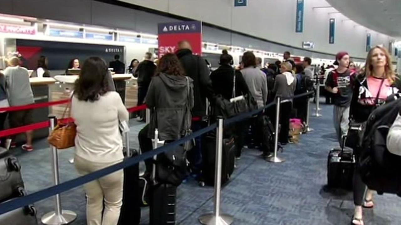 This image shows passengers waiting in long lines at the San Francisco International Airport as flights experienced delays due to gusty winds on May 20, 2016.