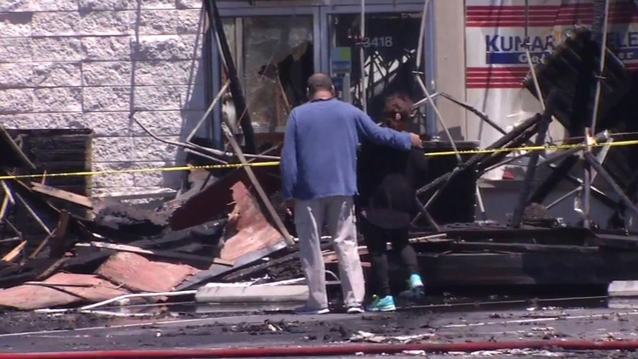 This image shows two people standing in front of a Santa Clara, Calif. shopping center that was destroyed in a fire on May 25, 2015.