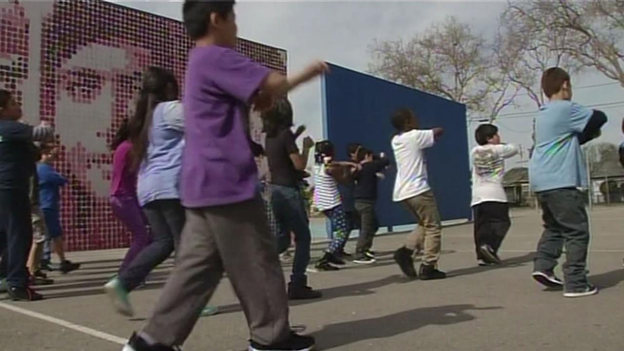 This image shows students at Burbank Elementary School in Hayward, Calif. practicing their performance of Everyday People with actor Tim Robbins.