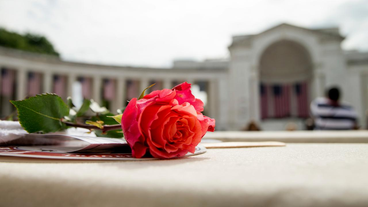 A rose is visible on a seat before President Barack Obama speaks at the Memorial Amphitheater of Arlington National Cemetery, in Arlington, Va., Monday, May 30, 2016.