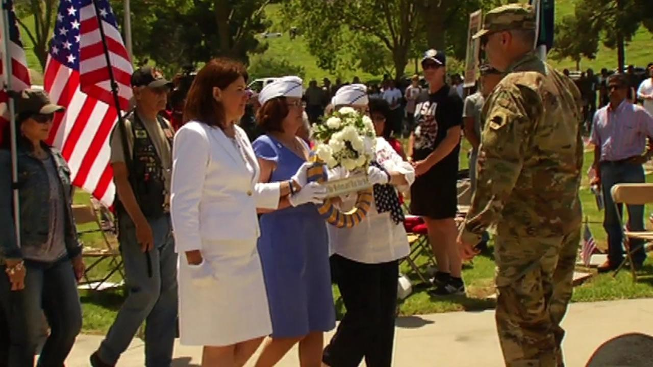 A group of people honor fallen troops on Memorial Day, Monday May 30, 2016.