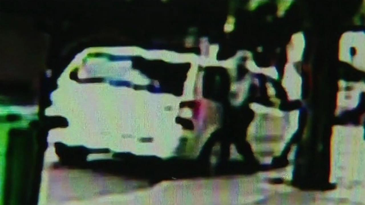 This image is a still from surveillance showing a suspect allegedly stealing an FBI agents gun from a parked car near Alamo Square in San Francisco.