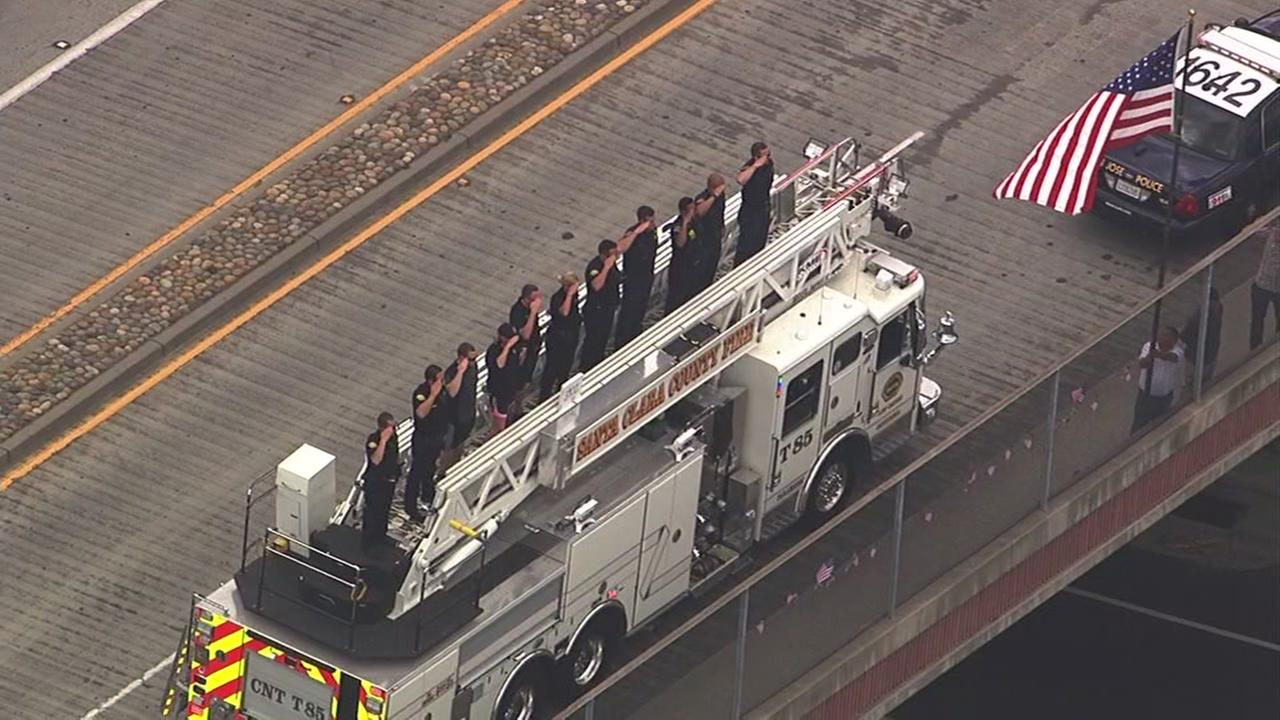 Firefighters give a salute as the procession for fallen San Jose police officer Michael Katherman drives by in San Jose, Calif. on June 16, 2016.