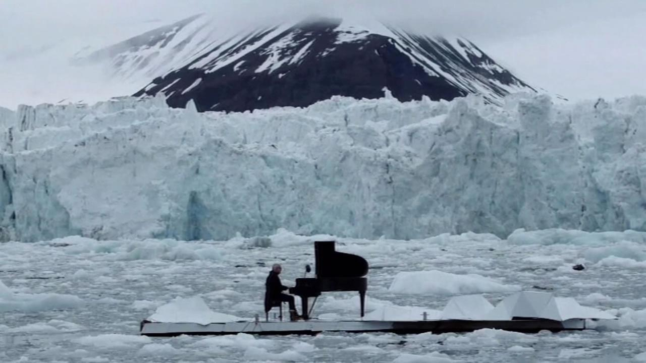 This image shows Italian pianists Ludovico Einaudi performing his piece Elegy For the Arctic on a floating platform on the Arctic Ocean.