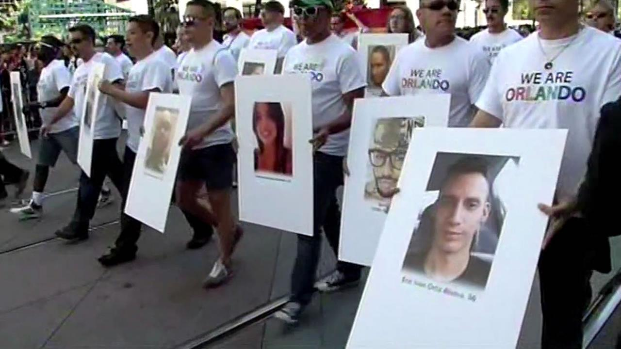 A large crowd holds up photos of the victims of the Orlando shooting during San Franciscos Pride Parade on Sunday, June 26, 2016.
