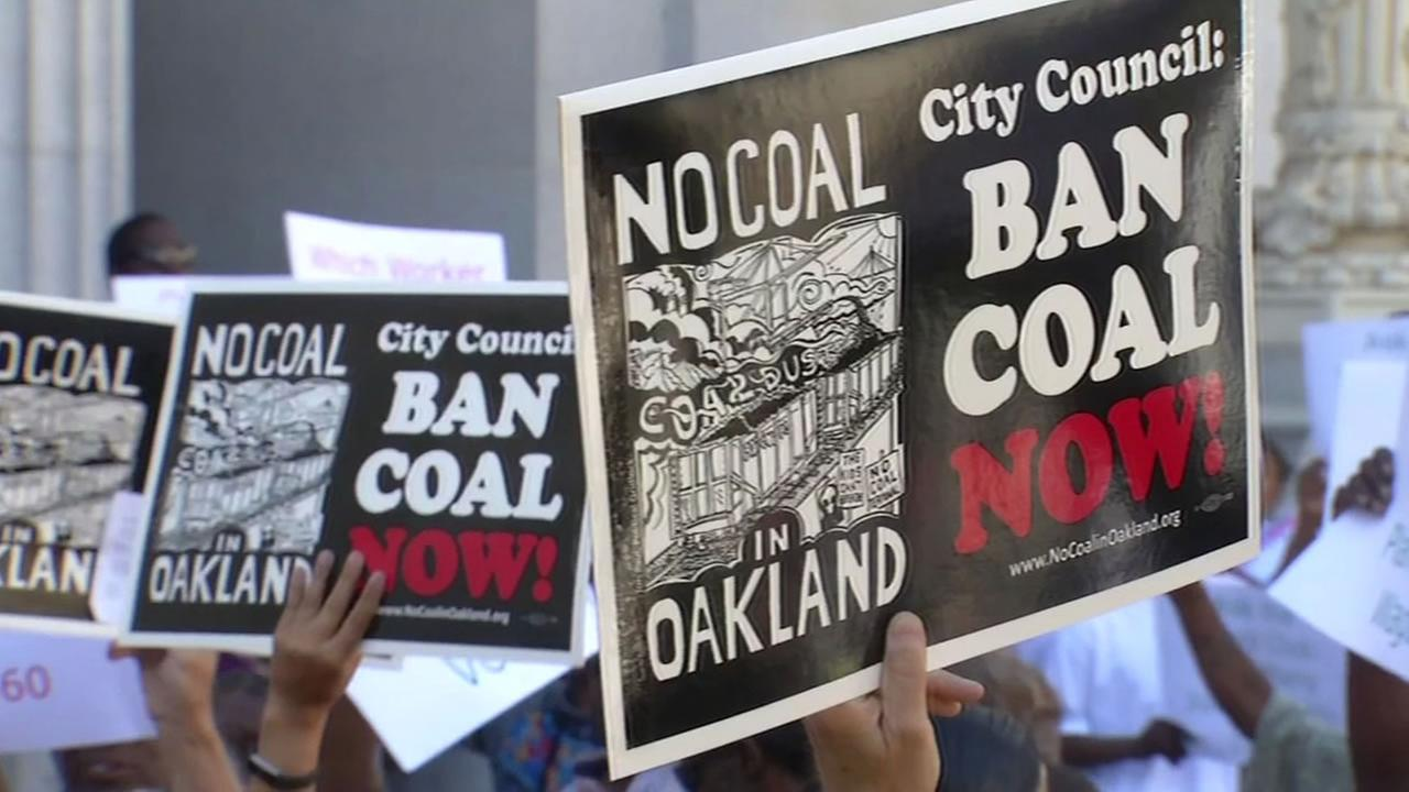 Voters hold up signs to ban coal from being exported in Oakland, Calif. on Monday, June 27, 2016.