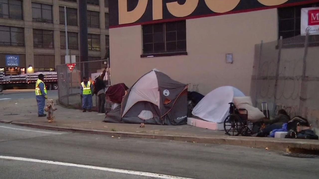 The image shows Department of Public Works workers on their morning cleaning sweep of homeless encampments in San Francisco on June 29, 2016.