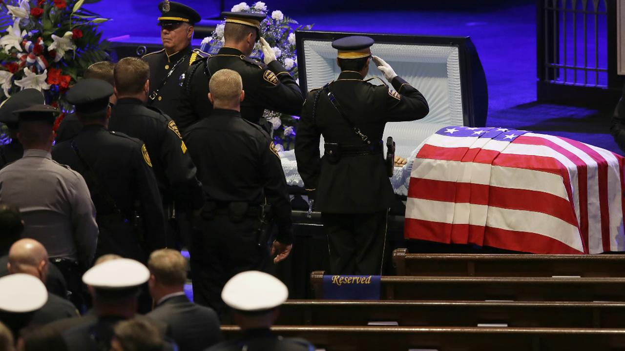 Law enforcement officer salute Dallas Police Sr. Cpl. Lorne Ahrens before his funeral service at Prestonwood Baptist Church in Plano, Texas, Wednesday, July 13, 2016.