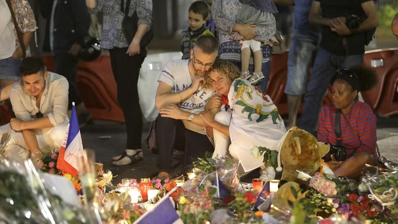 People lay flowers and light candles to honor the victims of an attack, on the Promenade des Anglais, near the area where a truck mowed through revelers in Nice July 16, 2016. ++